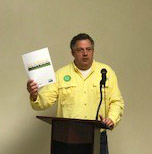 MK in yellow shirt stands at podium holding white piece of paper, NELA meeting 2018