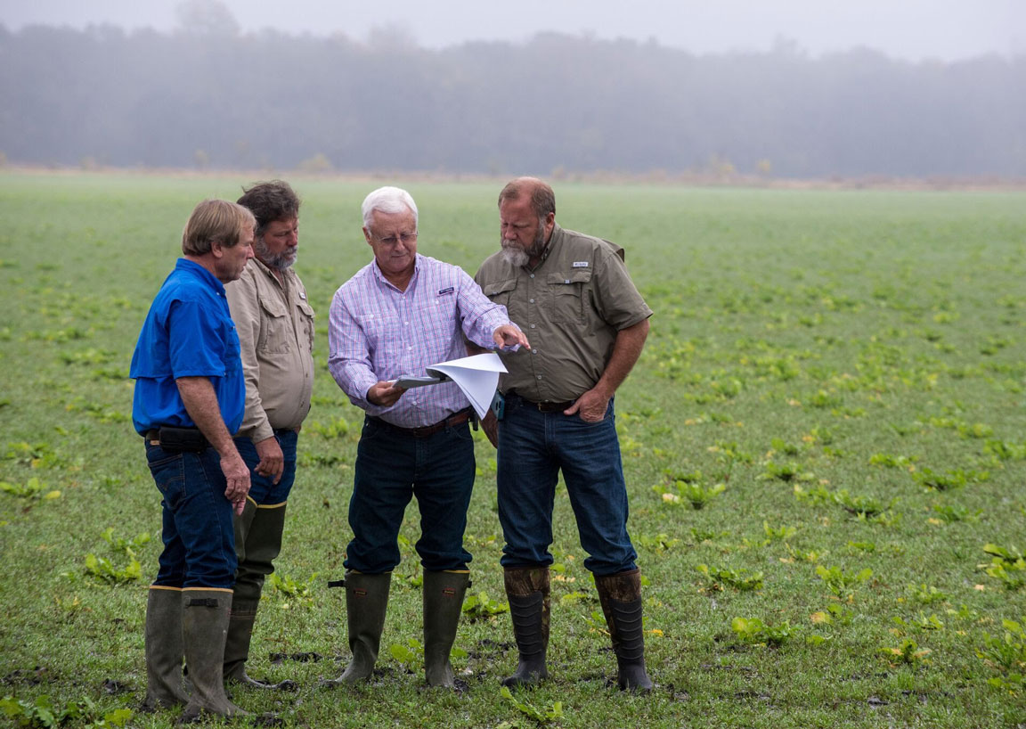 Durands-Honored-for-4R-Stewardship, standing in field looking a man holding soil charts