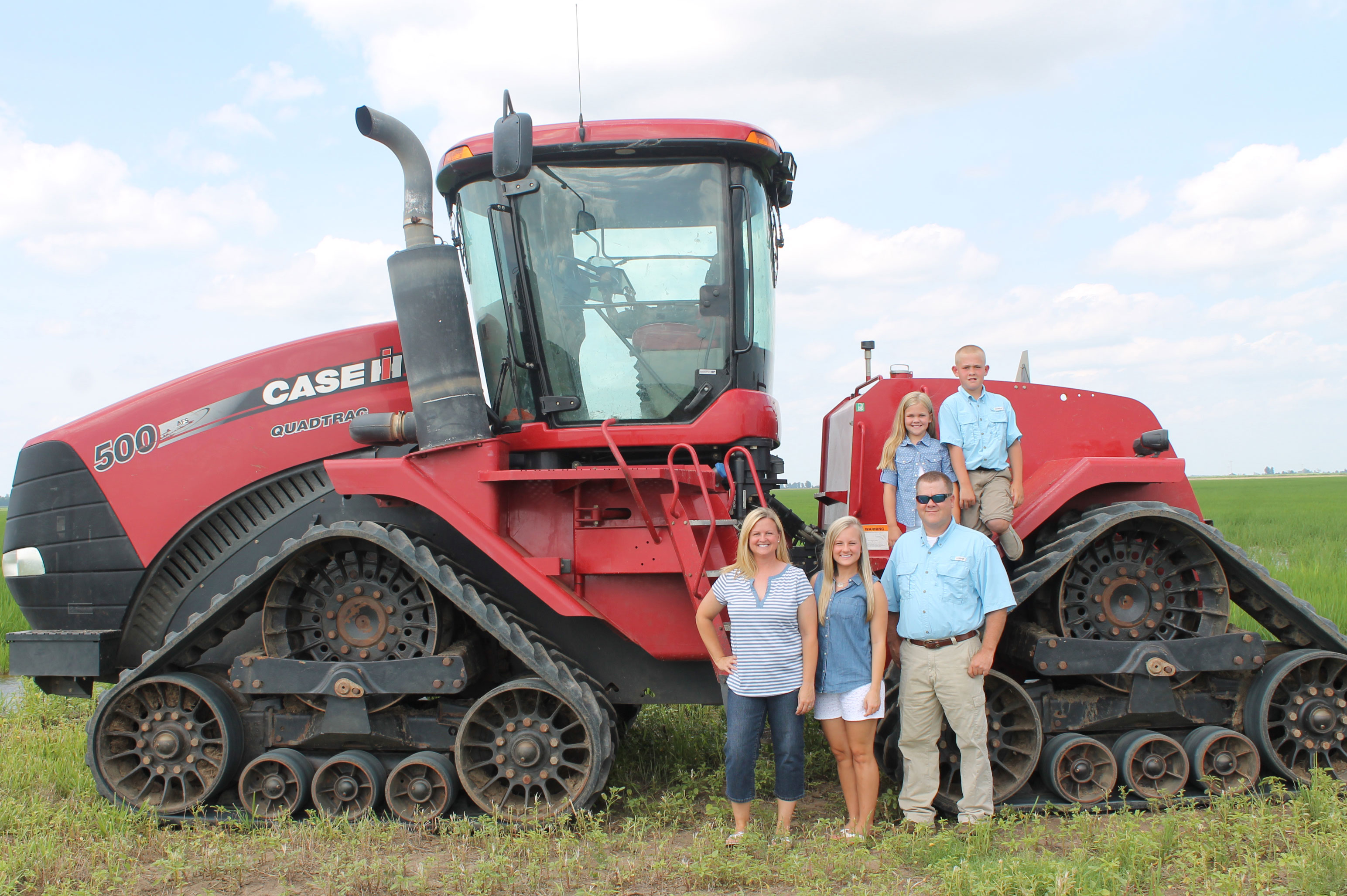 Farmer Rance-Daniels-&-Family,-stand in front of red combine in rice field