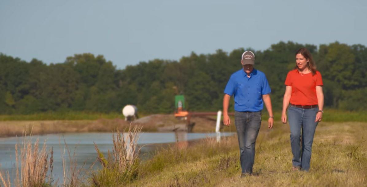 Jennifer-& Dylan-James-walk along retention pond on their AR rice farm